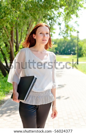 Pretty young woman walking with laptop under the hand. - stock photo