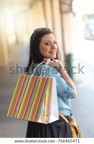 Pretty young woman walking with shopping bags in hand