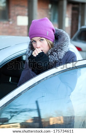 Pretty young woman warming her hands standing near the car - stock photo