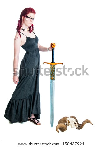 Pretty young woman warrior holding a sword with a rams horn on the ground isolated against a white background - stock photo