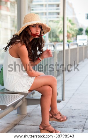 Pretty young woman wearing a hat and lowering her sunglasses while waiting for a bus to arrive in Nice, France. - stock photo