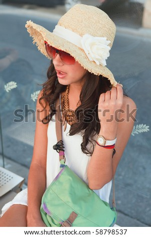 Pretty young woman wearing a hat and singing while waiting for a bus to arrive in Nice, France. - stock photo