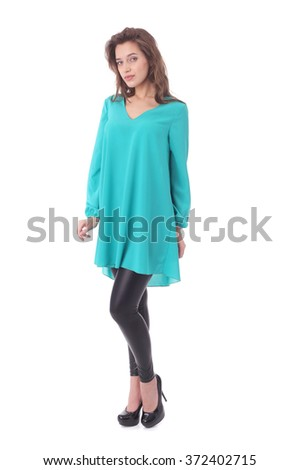 pretty young woman wearing green tunic and black pants - stock photo