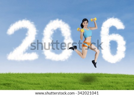 Pretty young woman wearing sportswear, holding two dumbbells and jumping at field with numbers 2016 - stock photo