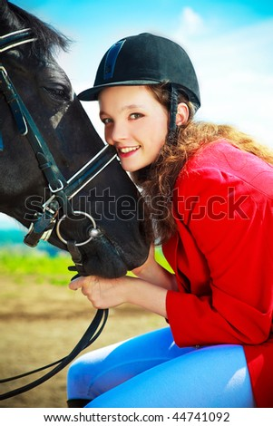 pretty young woman with a black horse - stock photo