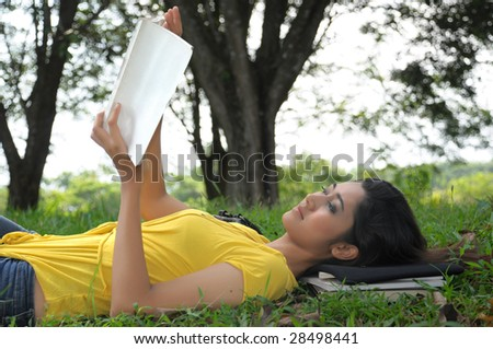 pretty young woman with a book on the grass - stock photo