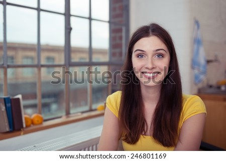 Pretty young woman with a happy bright smile sitting in her apartment alongside a window overlooking an urban street