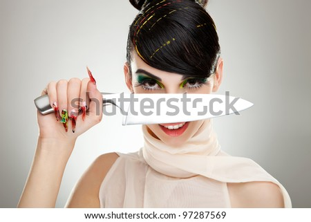 Pretty young woman with a knife over her face - stock photo