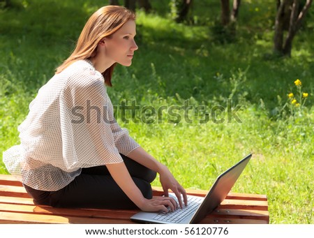 Pretty young woman with a laptop at park