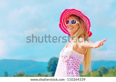 Pretty young woman with arms raised - stock photo