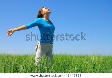 Pretty young woman with arms raised standing on Meadow - stock photo