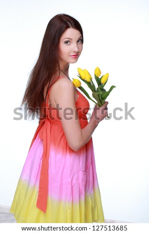 Pretty young woman with beautiful long hair in a summer dress on white background/Beautiful girl holding a bouquet of tulips on Holiday