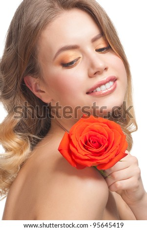 Pretty young woman with beautiful make-up and perfect healthy skin with rose in her hand - stock photo