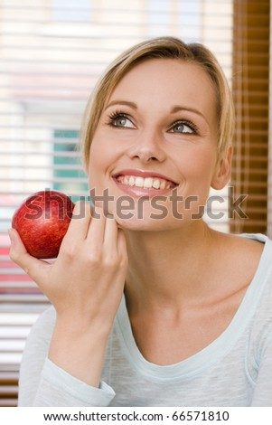 Pretty young woman with beautiful white teeth holding an apple in her hand - stock photo