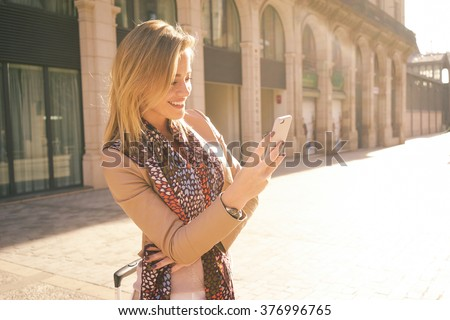 Pretty young woman with blonde hair chatting on the smart-phone at the city street background. pretty girl having smart phone conversation in sun flare.  - stock photo
