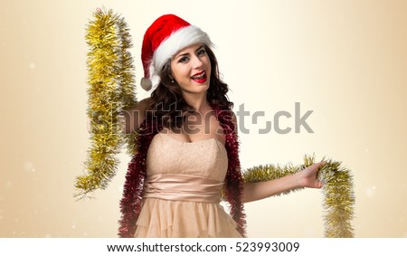 Pretty young woman with christmas wreaths on ocher background