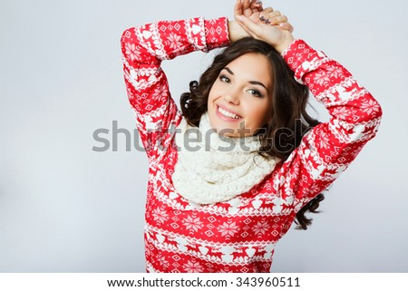 Pretty young woman, with dark curly hair, wearing in red Christmas sweater and white scarf, posing with hands over her head, on the white background, in studio, waist up - stock photo