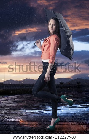 pretty young woman with dark umbrella, her body is turned in profile and she looks in to the lens - stock photo