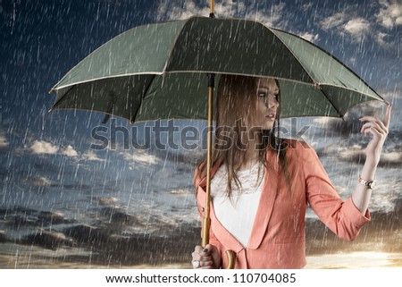 pretty young woman with green umbrella, under summer rain during a beautiful sunset - stock photo