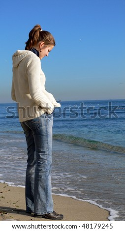 Pretty young woman with hands in pockets standing alone on a beach deep in thought