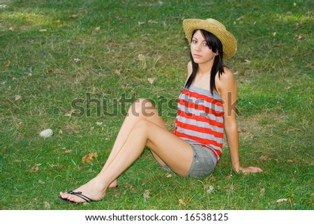 Pretty young woman with hat sitting on a grass field - stock photo