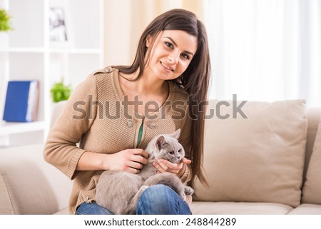 Pretty young woman with her cat on the couch at home. - stock photo