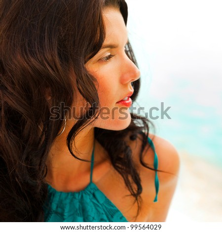 Pretty young woman with hot look and sexy smile sitting on beach near pool - stock photo