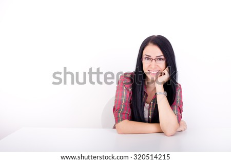 Pretty young woman with long black hair and with glasses leaning on arm on white desk. Isolated on white background - stock photo
