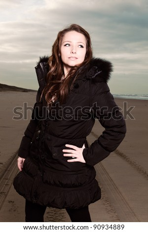 Pretty young woman with long brown hair wearing black winter coat on the beach. Autumn. Cloudy sky.