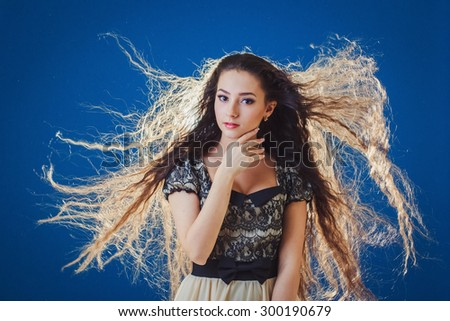 Pretty young woman with long hair on blue background - stock photo