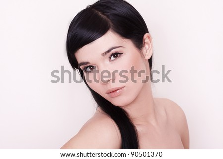 Pretty young woman with long straight black hair looking at camera, isolated on white background