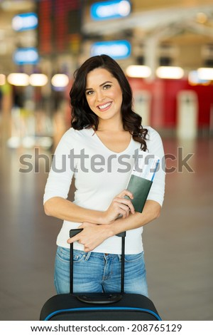 pretty young woman with luggage bag at airport - stock photo