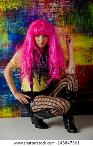 Pretty young woman with pink hair and stockings kneels down in front of a colorful abstract background. - stock photo