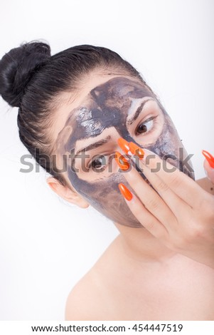 Pretty young woman with red long nails applying mask to face skin. Isolated on white background - stock photo
