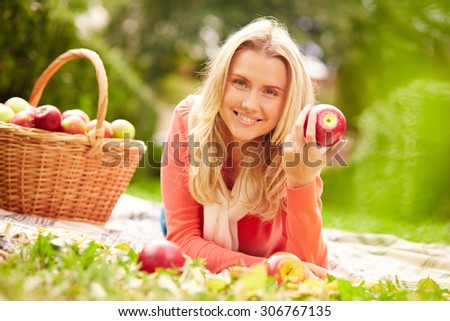 Pretty young woman with ripe apple looking at camera outdoors - stock photo