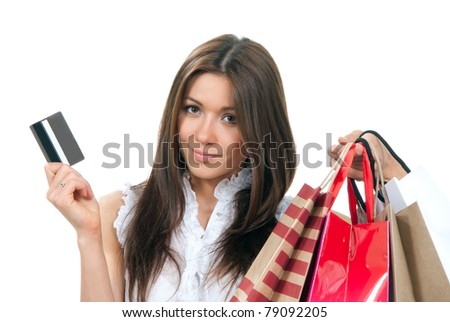 Pretty young woman with shopping bags, credit gift card in one hand buying presents, smiling and looking at the camera isolated on a white background - stock photo