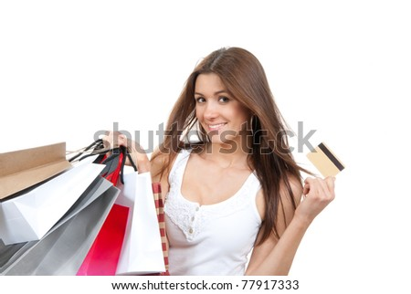 Pretty young woman with shopping bags, credit gift card in one hand buying presentsin supermarket, smiling and looking at the camera isolated on a white background - stock photo