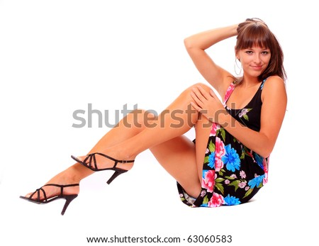 Pretty young woman with slim long legs dressed in luxury evening dress. Fashion shot, great fot calendar. - stock photo