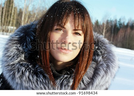 Pretty young woman with snowflake on her nose