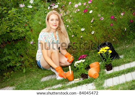Pretty young woman with tools in the garden - stock photo