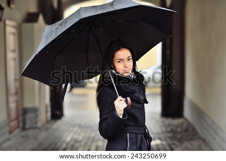 Pretty young woman with umbrella - stock photo