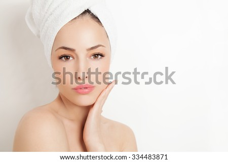 pretty young woman with white towel on her head and no makeup, studio portrait