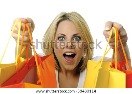 Pretty young woman with yellow and orange shopping bags - stock photo