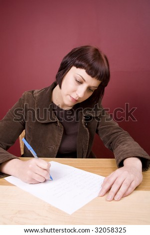 Pretty, young woman writing the list in a home environment.