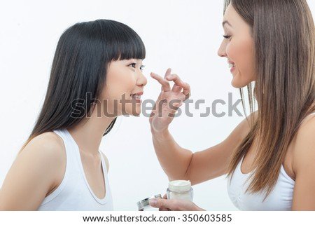 Pretty young women are standing and smiling. The Caucasian girl is applying cream on face of her asian friend. Isolated on background - stock photo
