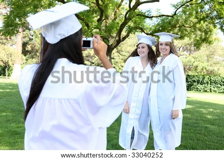 Pretty young women at graduation taking a picture - stock photo