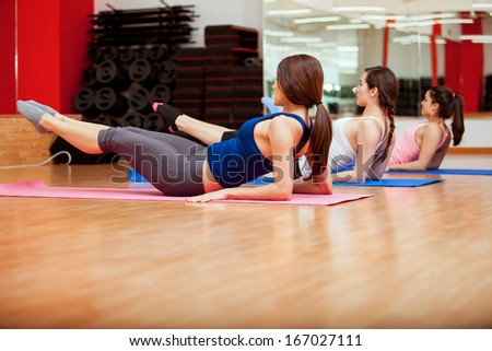 Pretty young women doing some crunches to strengthen their core at a gym - stock photo