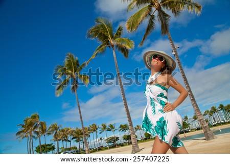 Pretty young women relax on Hawaiian palm beach in sarong. Model enjoying morning sun. Happiness bliss freedom concept, summer holidays travel. Oahu island, Hawaii, USA. - stock photo