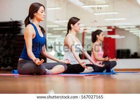 Pretty young women relaxing and meditating in their yoga class at a gym - stock photo