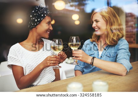 Pretty young women toasting each other with glasses of white wine as they meet up in a pub for a relaxing chat - stock photo